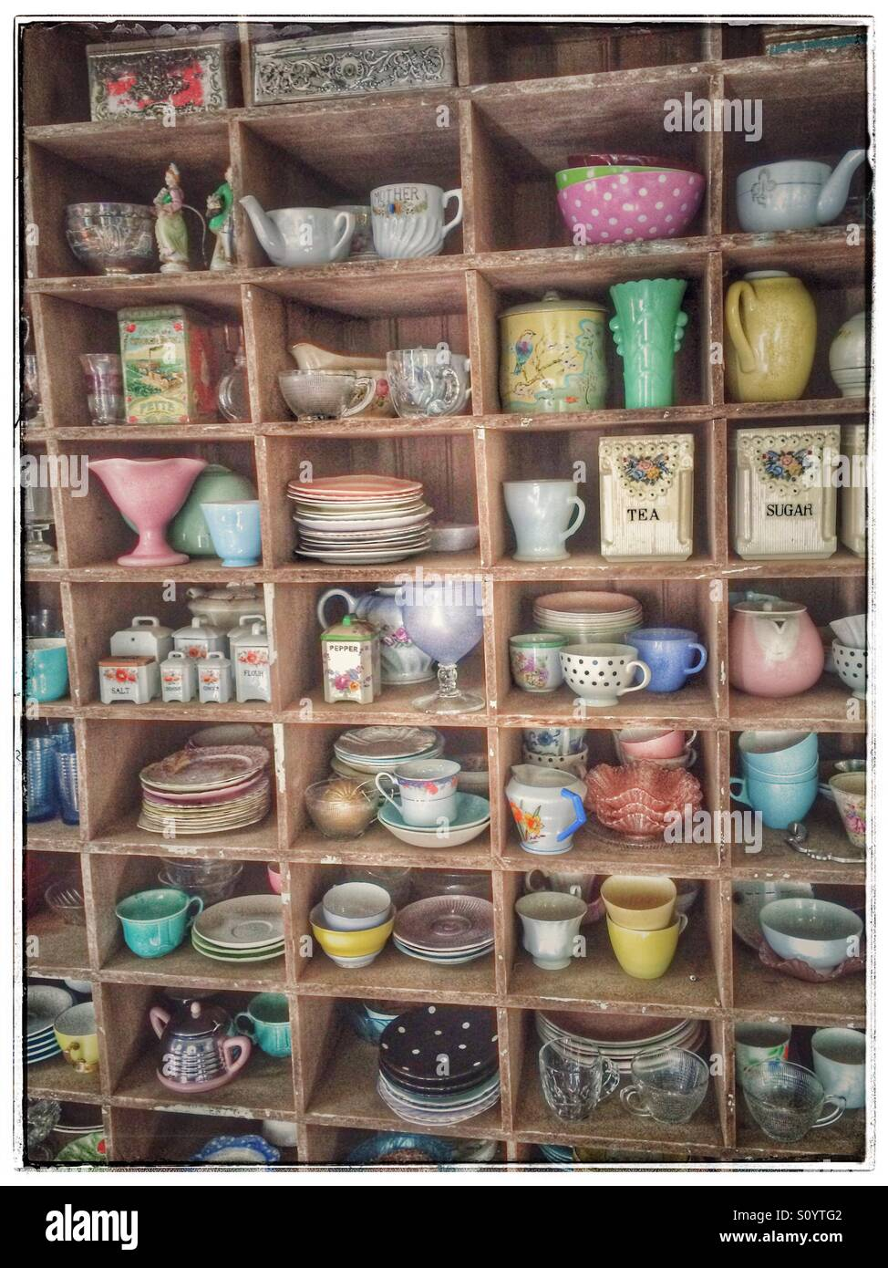 Shelf with vintage cups and saucers on display. - Stock Image