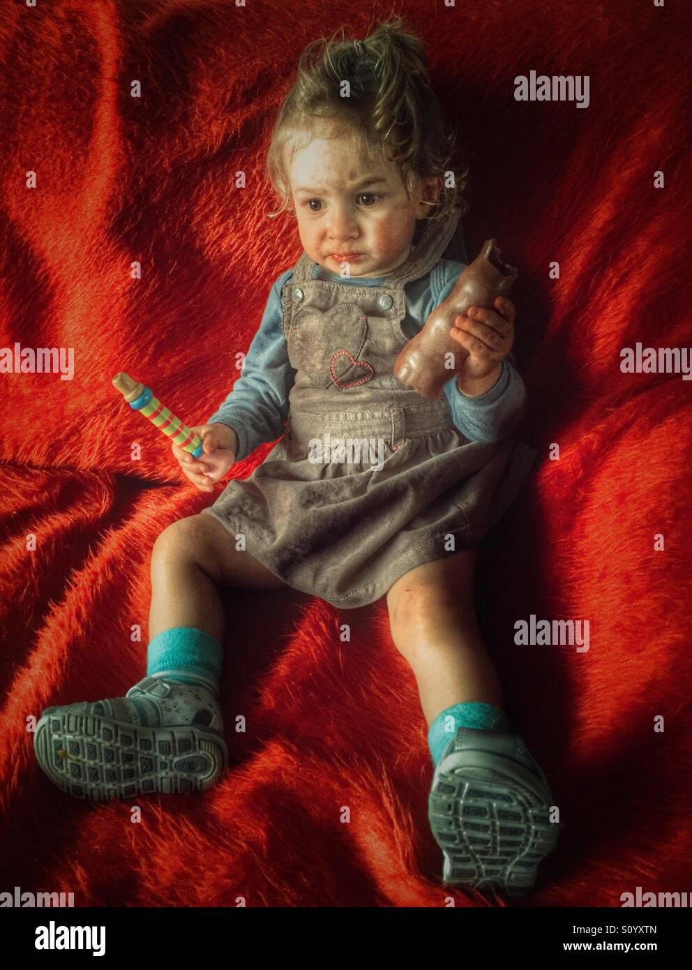 18 months baby girl sitting on sofa and eating chocolate - Stock Image