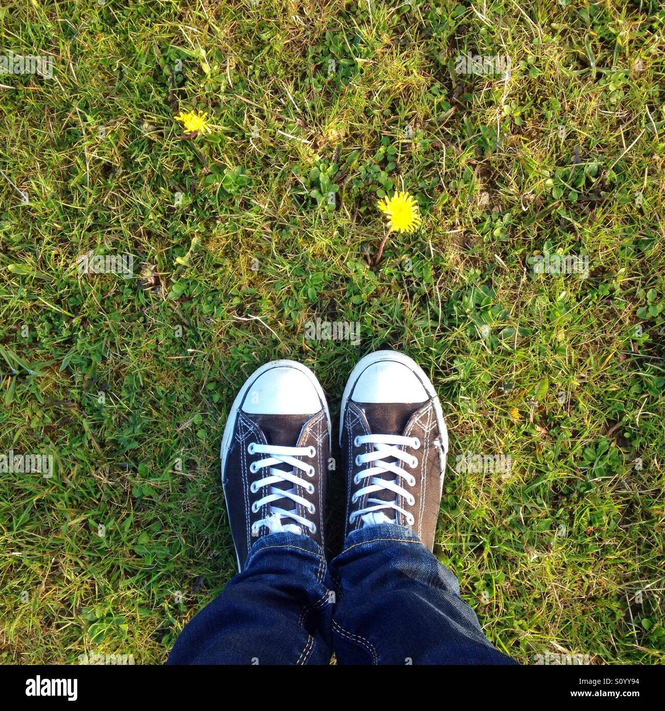 First signs of spring, view of feet on grass - Stock Image