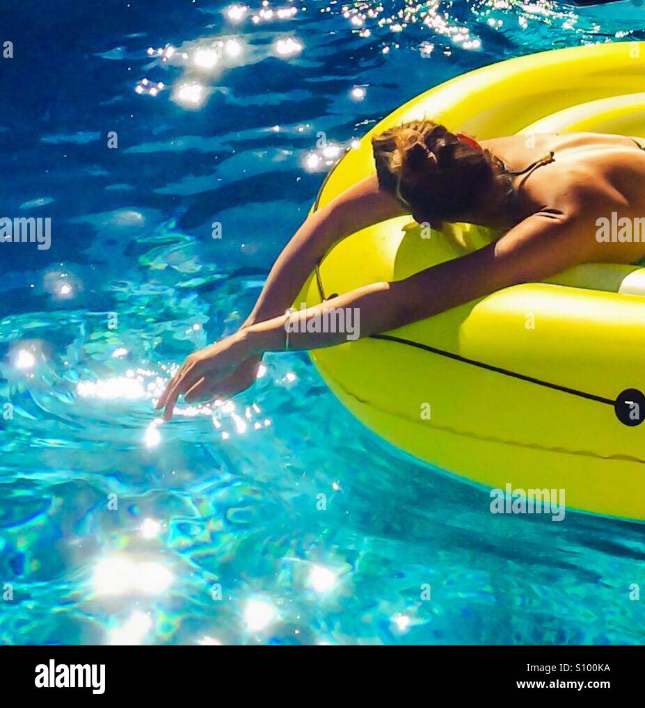 Woman sunbathing on a floating mat in blue waters. Stock Photo