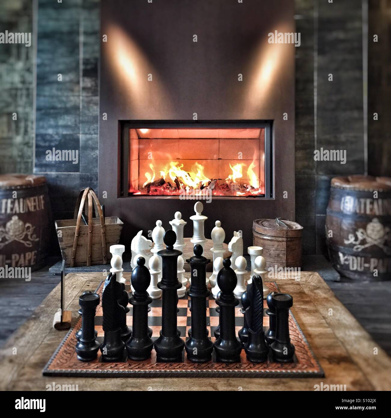 Game of chess in front of cosy fire in pub Stock Photo