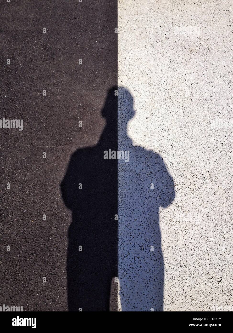 Man's shadow on two tone surface - Stock Image