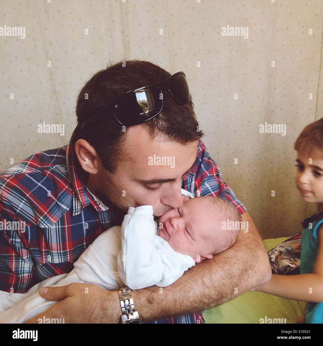 New born baby. Father and kids in hospital,first moment with baby - Stock Image