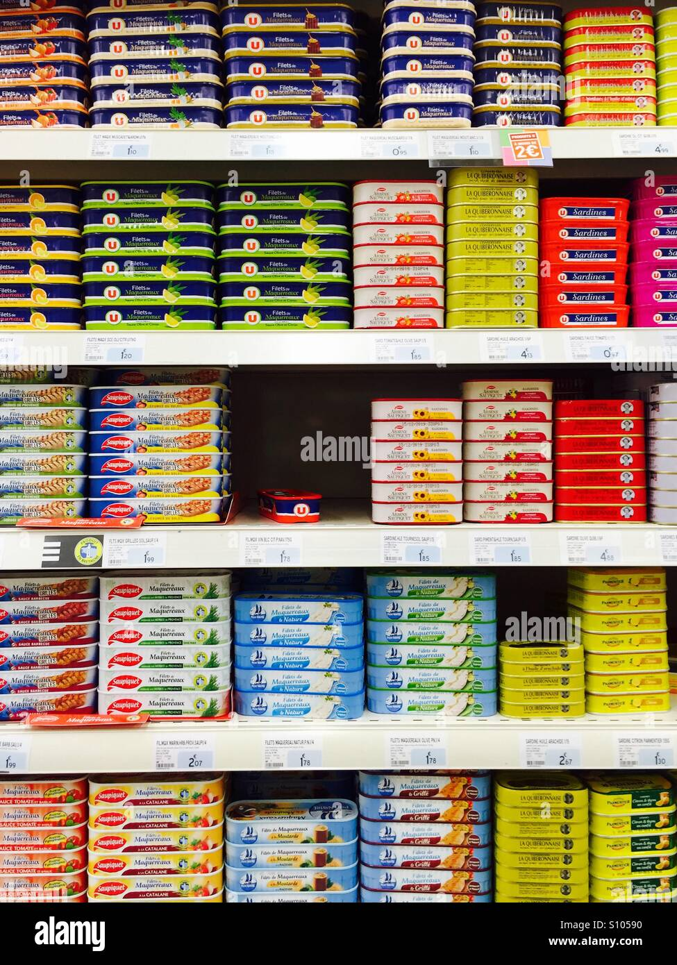 Tins of mackerel stacked on the shelves of a French supermarket - Stock Image