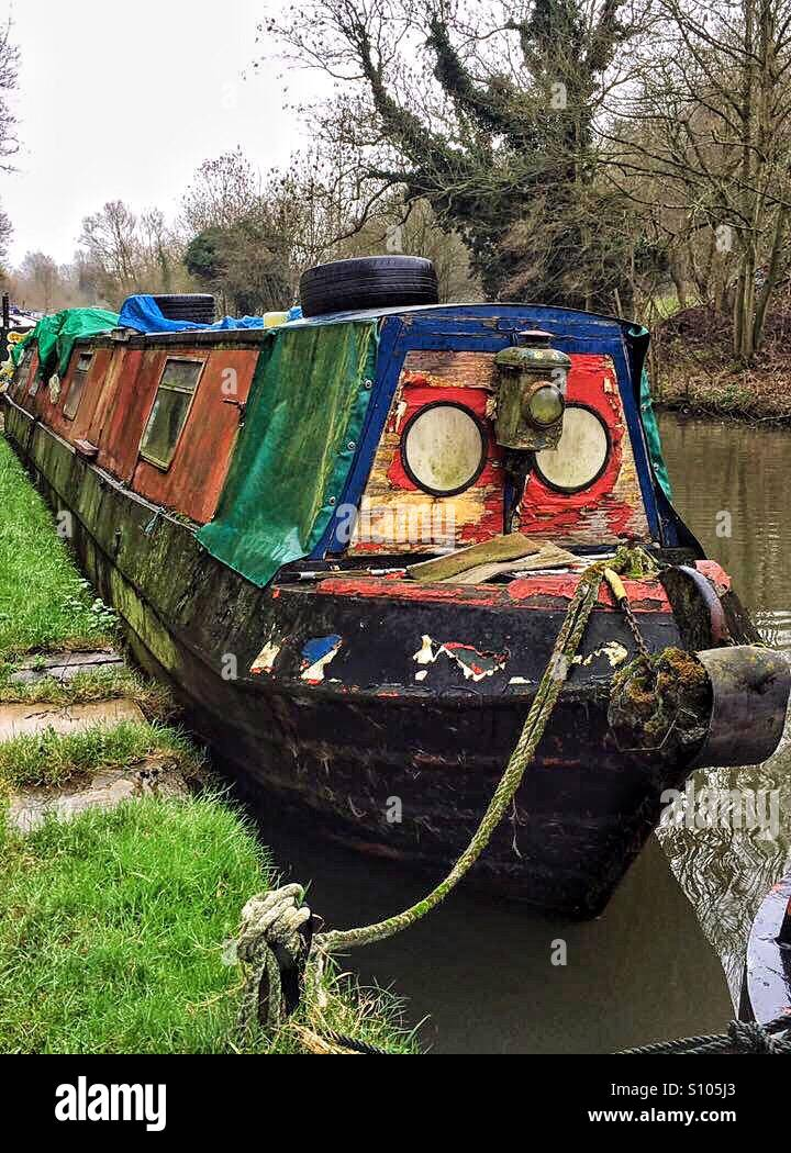 A dilapidated brightly painted narrowboat on the Grand Union Canal near Rickmansworth, Hertfordshire, England - Stock Image