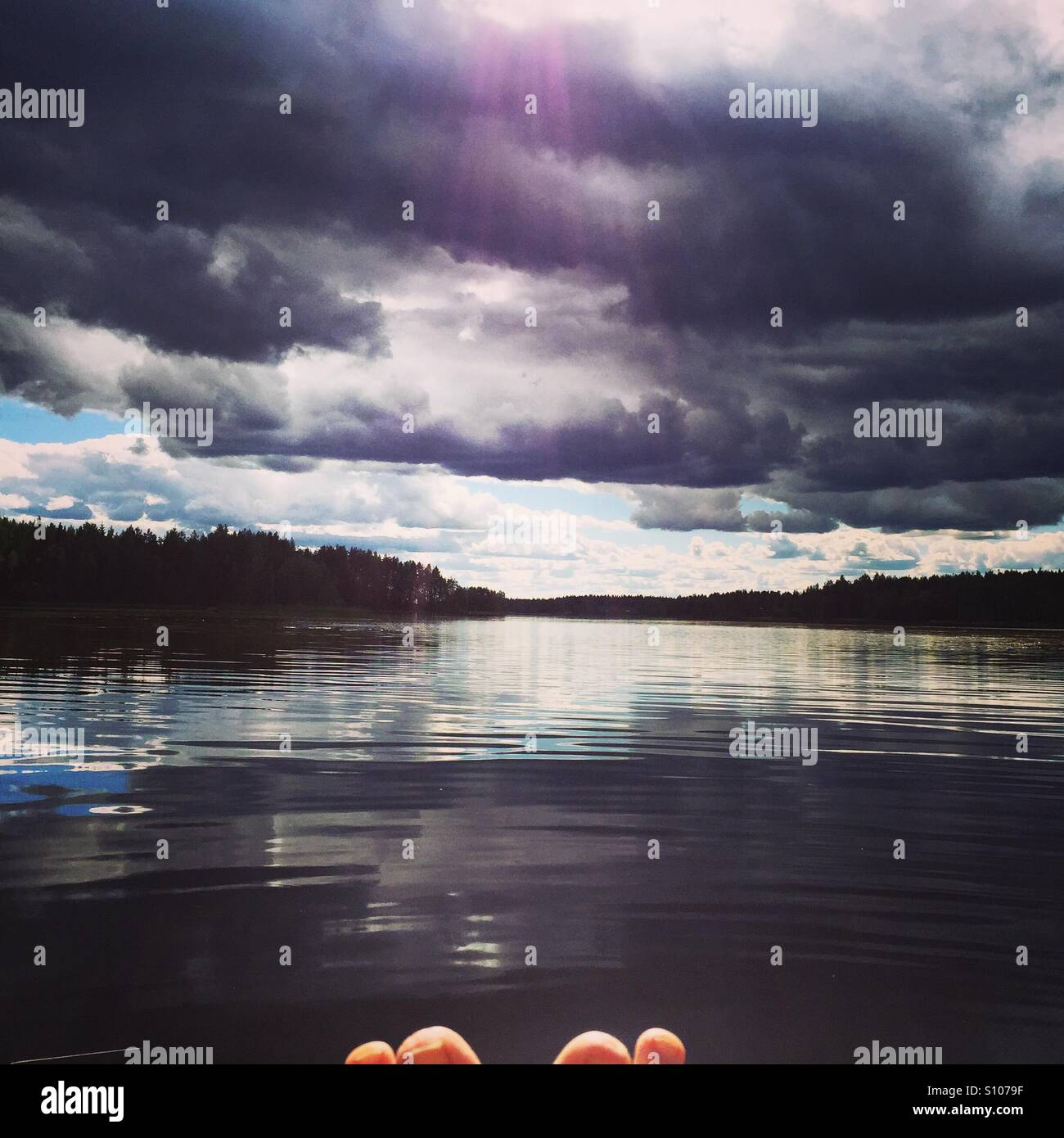 Summer day with dramatic sky and tip of toes - Stock Image