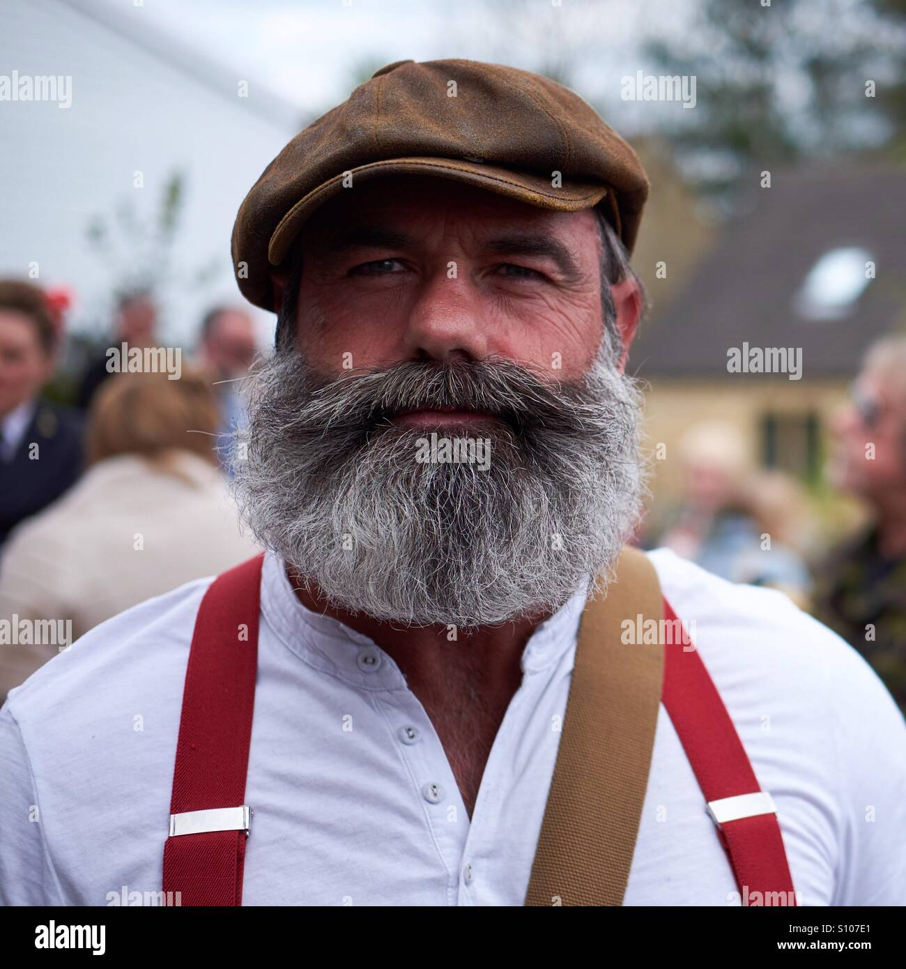 Portrait of a man with a substantial greying beard and flat cap wearing a grandad shirt and red braces. - Stock Image