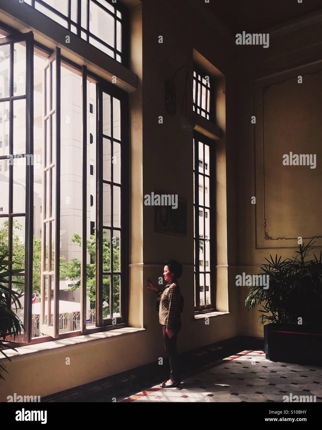 Woman look outside a window - Stock Image