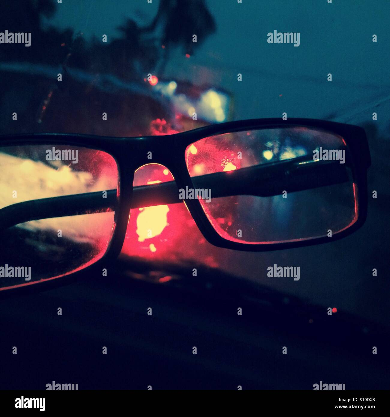 View through a spectacle of a moving road in a rainy night - Stock Image