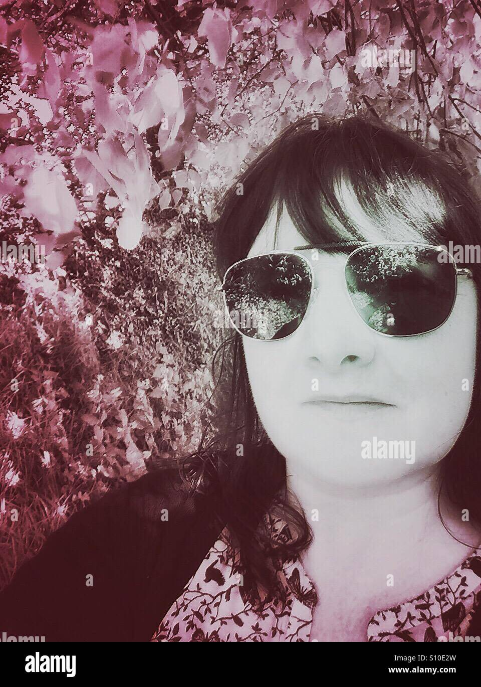 Selfie of woman against Spring hedgerow. - Stock Image