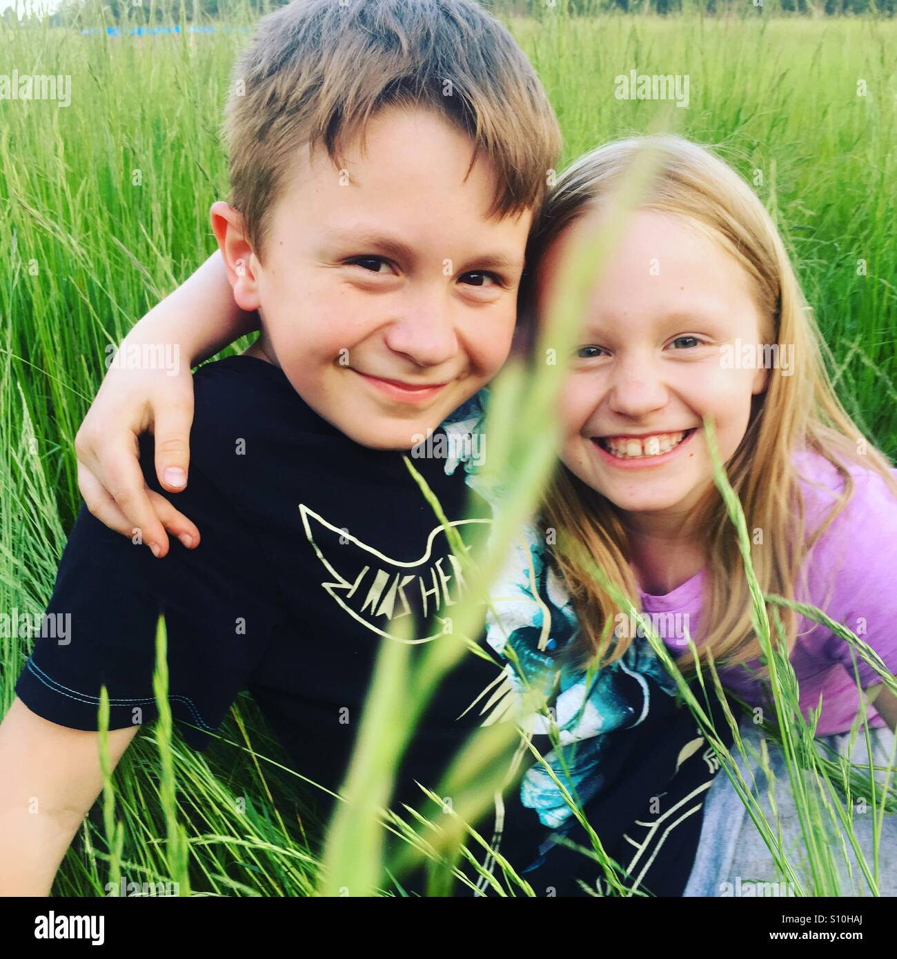 Happy siblings hugging each other and smiling, sitting outside in a tall green grass on a fine, beautiful, sunny, Stock Photo