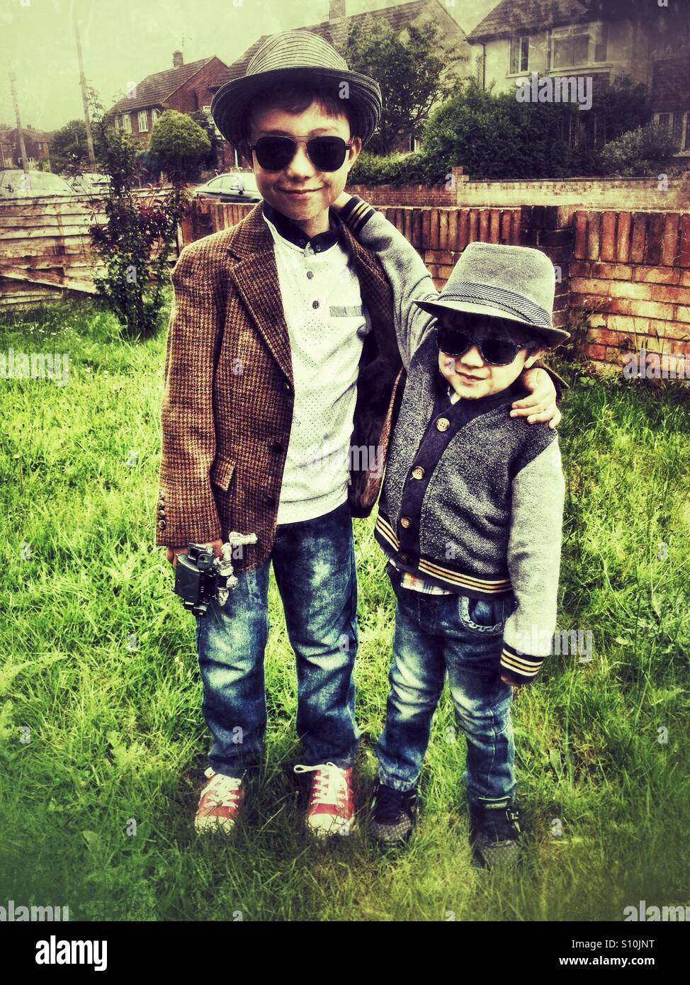 Young brothers wearing hats and sunglasses. Stock Photo