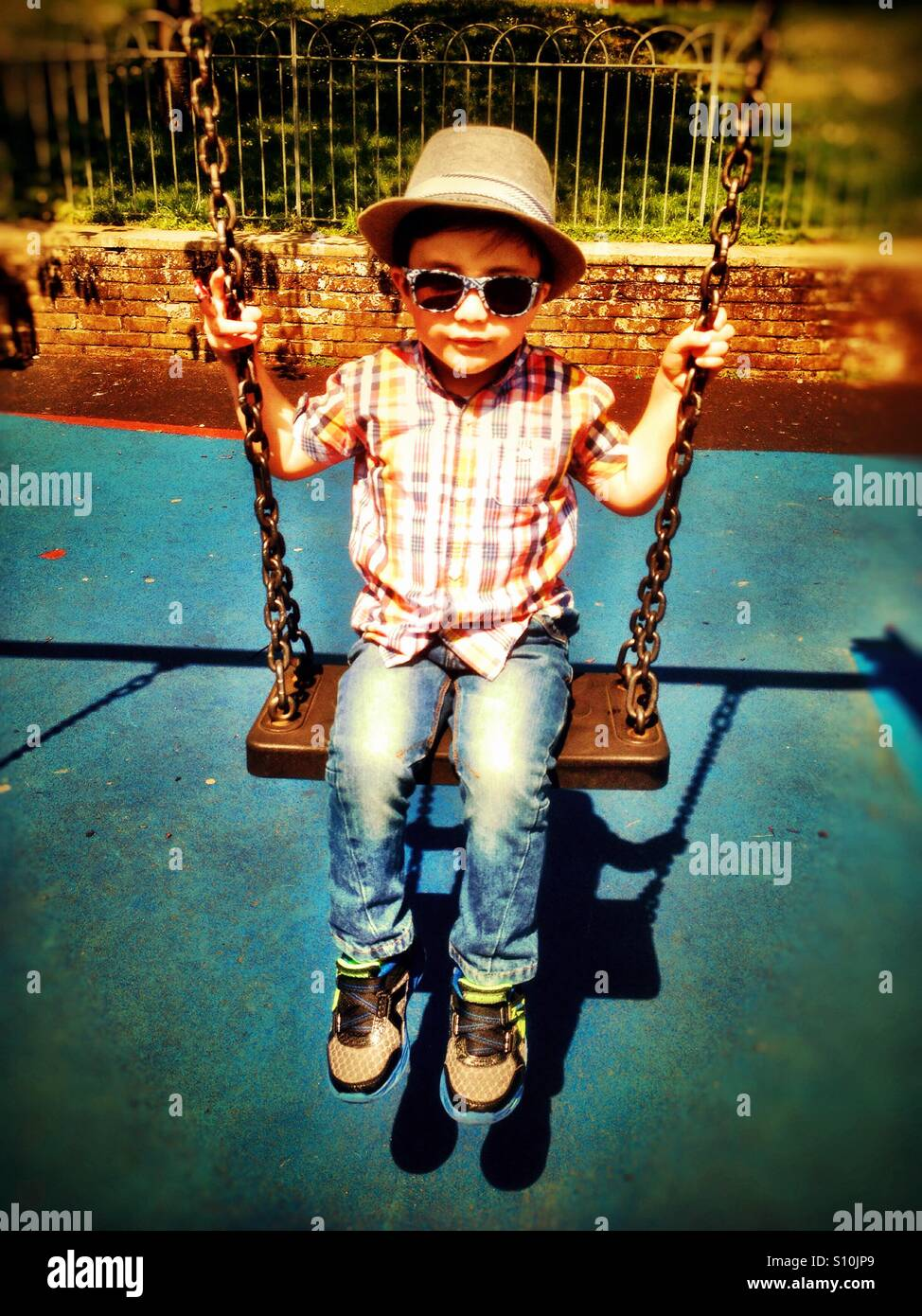 A young boy wearing hat and sunglasses plays on s swing in the park. - Stock Image