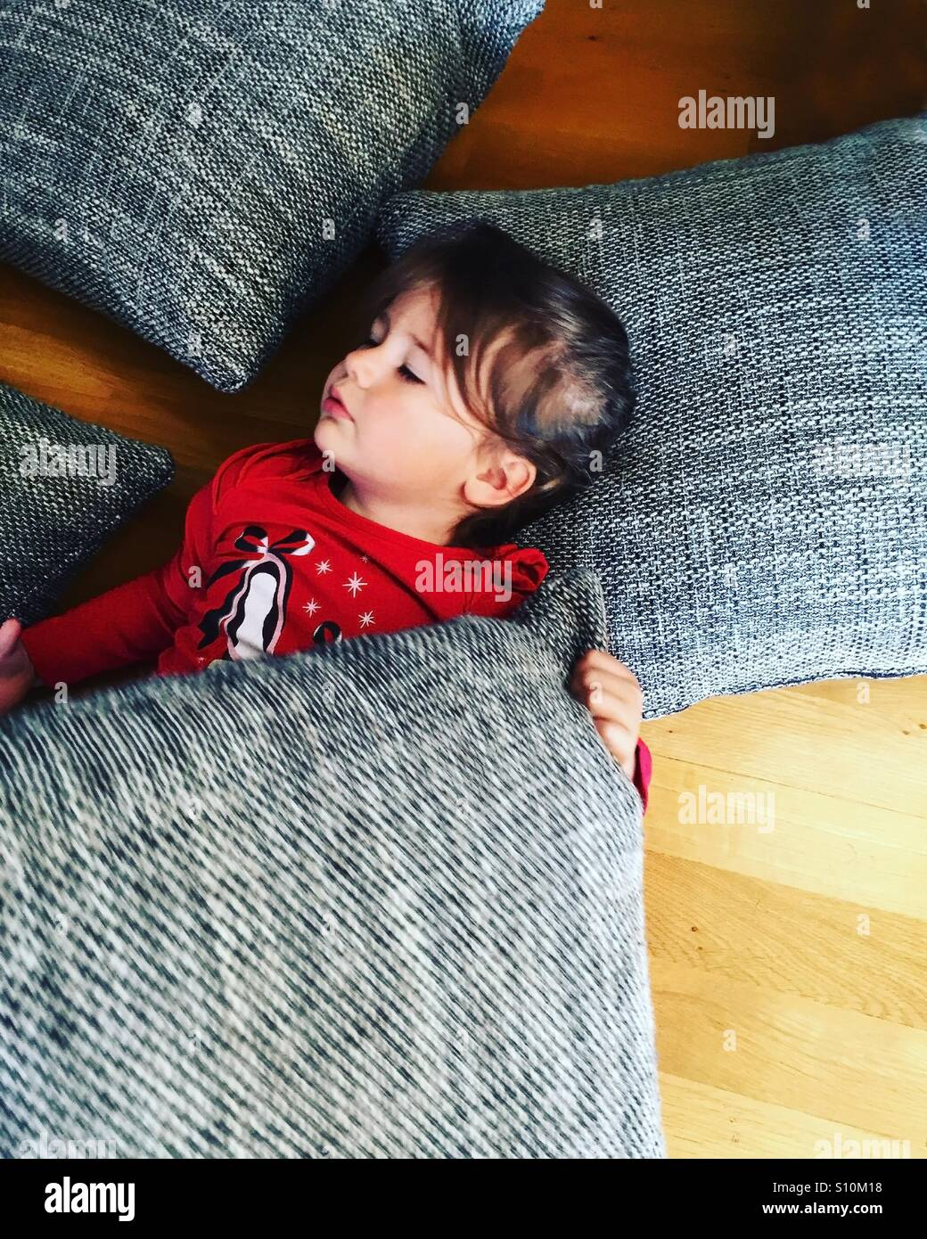 Little girl sleeping on floor with many pillows around Stock Photo ...