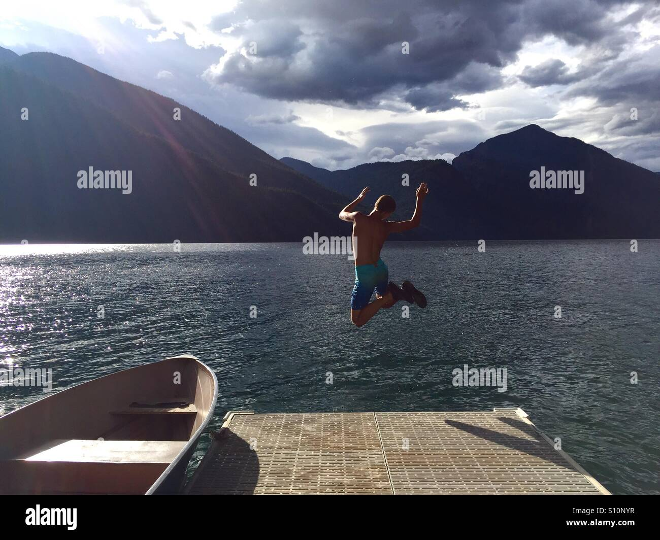 Teen boy leaping off dock into lake. - Stock Image