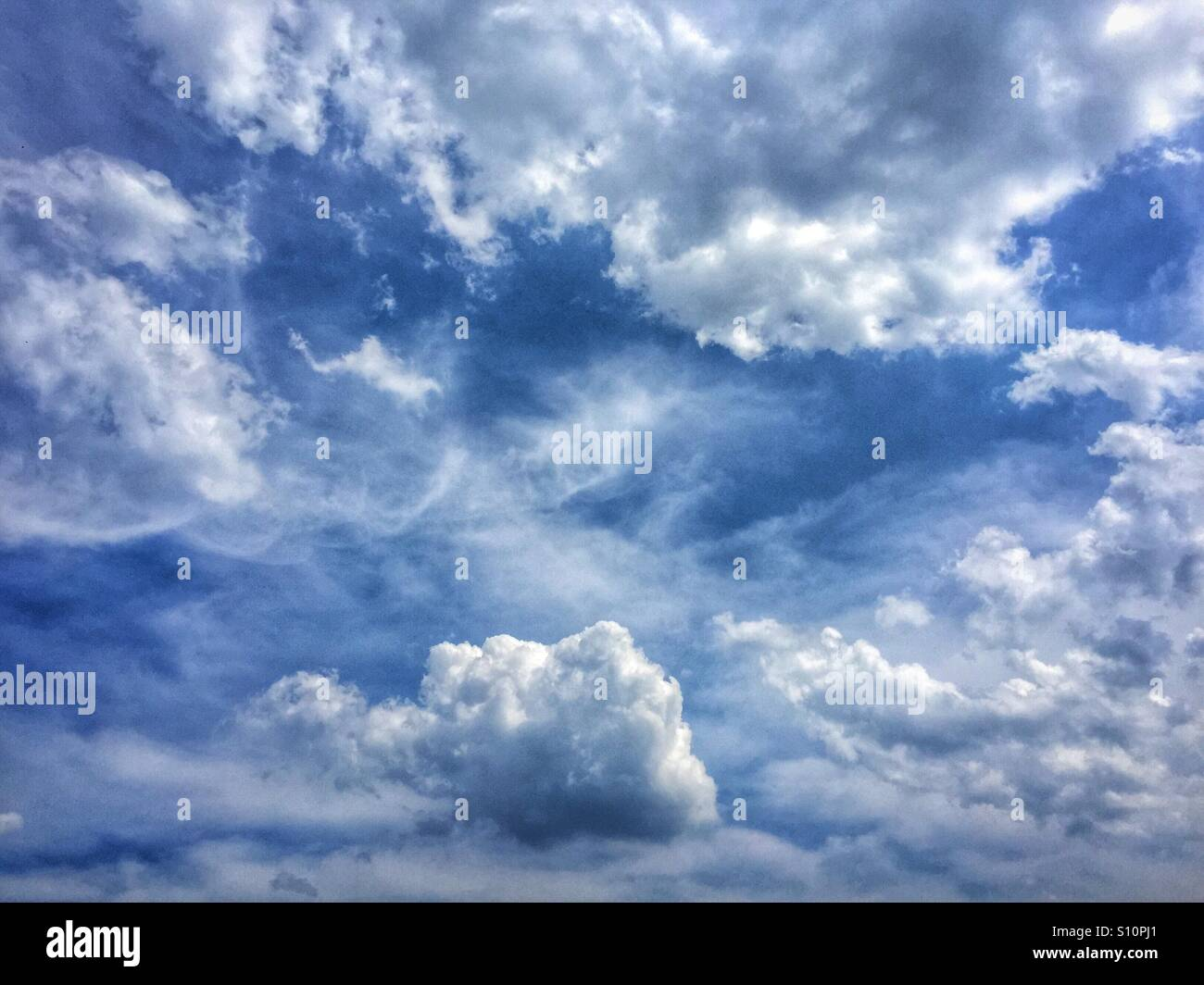 Beautiful fluffy clouds in a see blue sky on a summer day looking like heaven - Stock Image