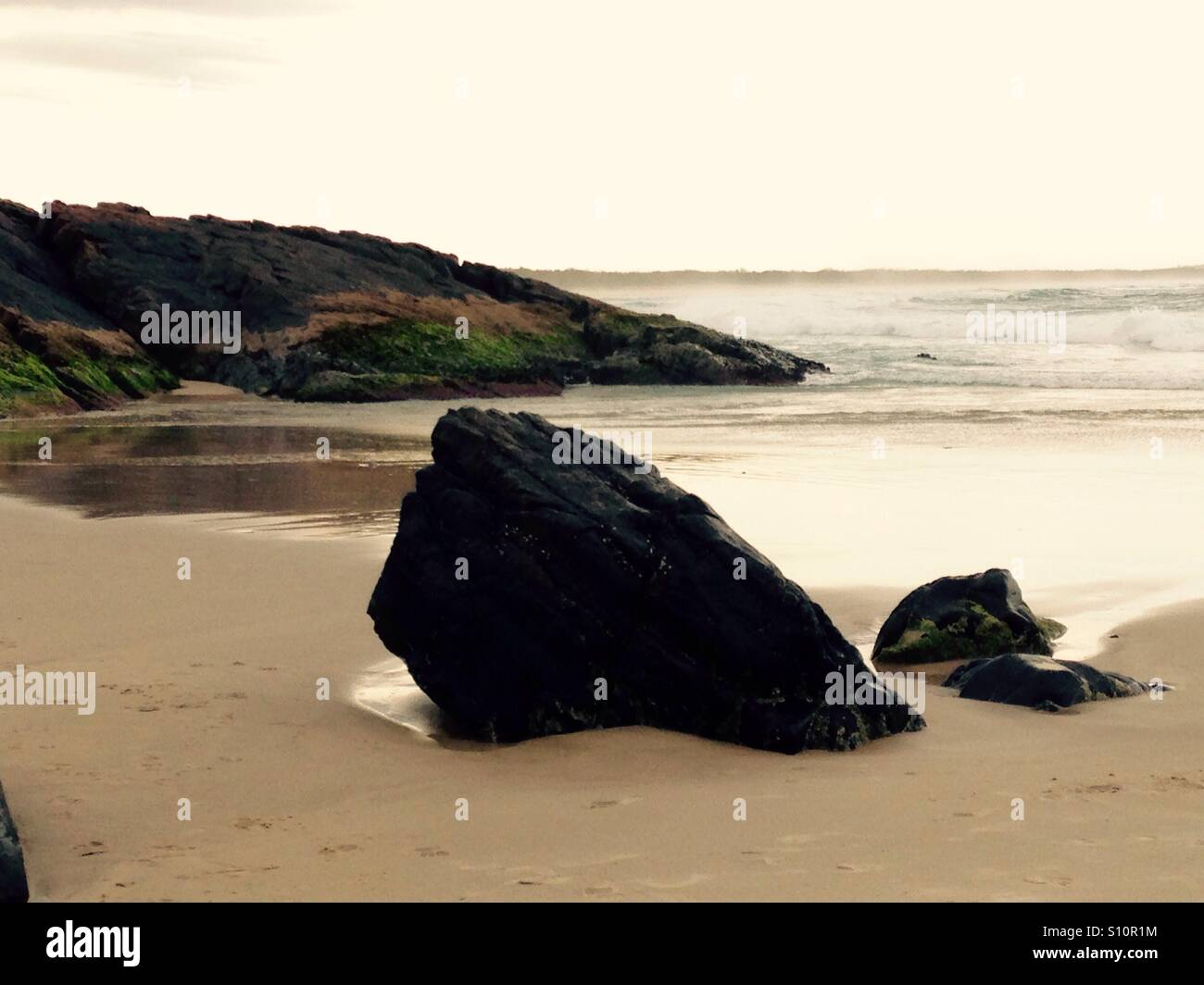 Sturdy Rock by the Beach Side, the power of gentle waves wearing away at a steadfast Rock over Time, Patience. - Stock Image