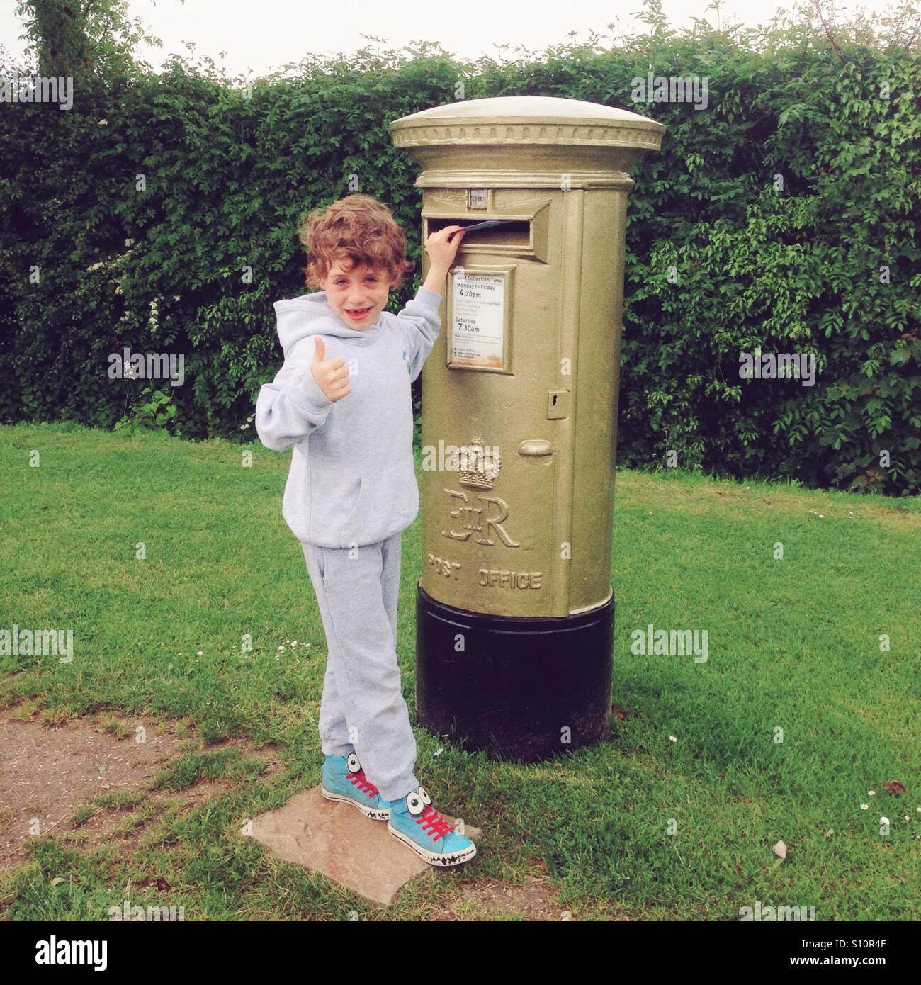 Seven year old boy posting a letter in a gold Olympic postbox, Bentworth, Hampshire, England, United Kingdom. - Stock Image