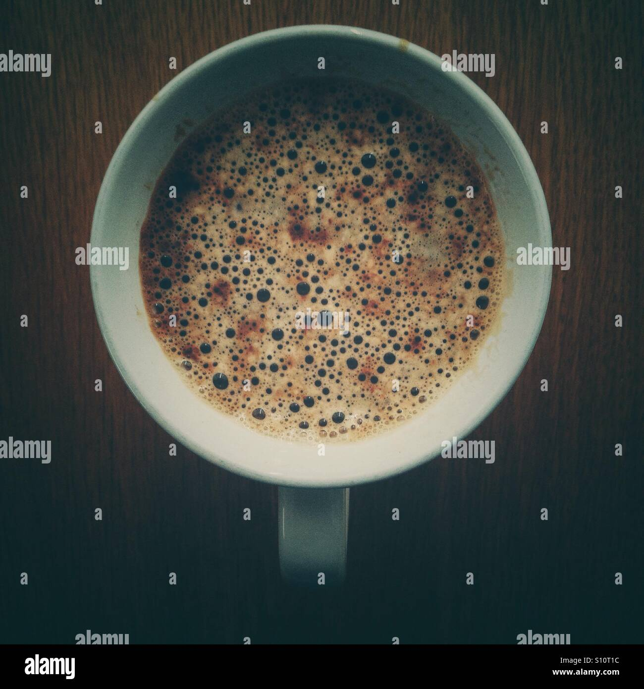 Dark coffee with bubbles. - Stock Image
