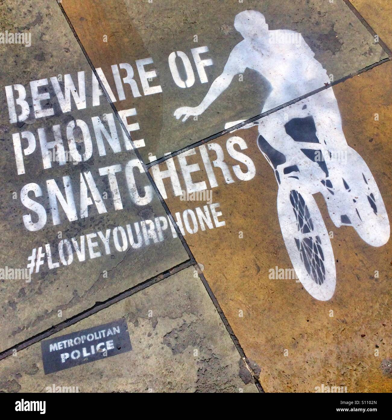Beware of the Phone Snatchers stencil on a street in central London. - Stock Image