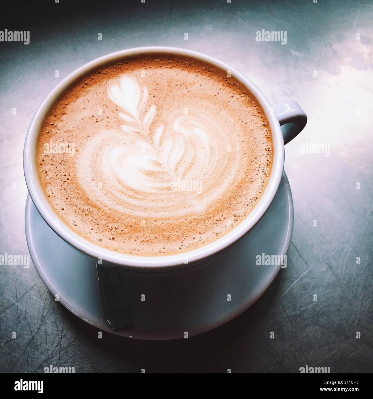 An overhead close-up shot of a fresh latte coffee beverage on a metal table top surface. A simple, clean composition. - Stock Image