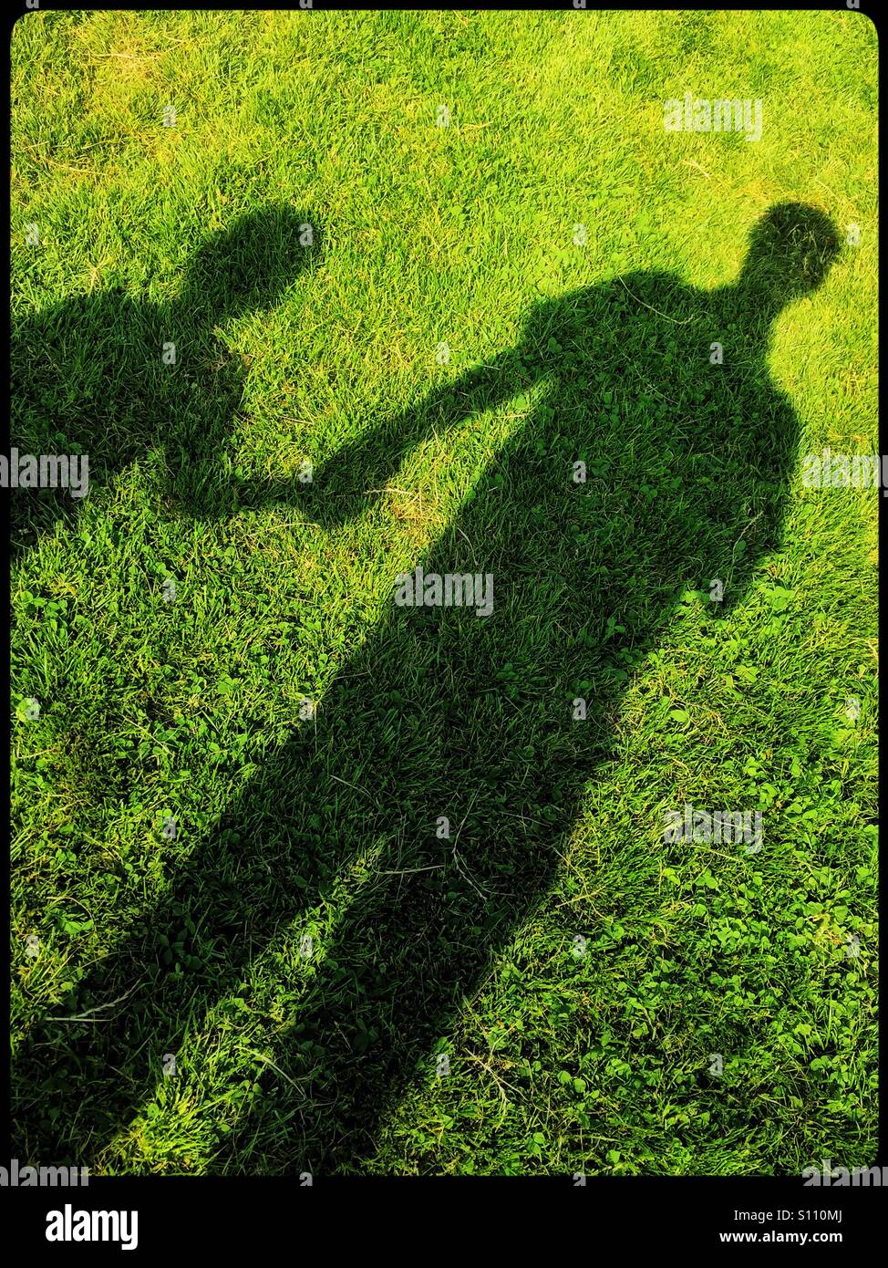 Shadows on the grass of a man and a boy, both holding hands. Is it Father and Son happy together OR is a Paedophile - Stock Image