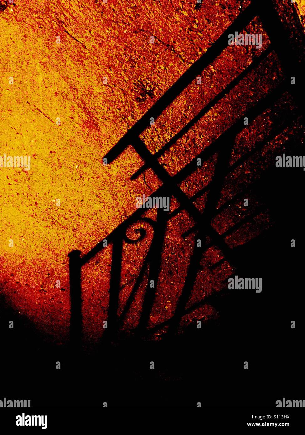 Fence shadow and orange light - Stock Image