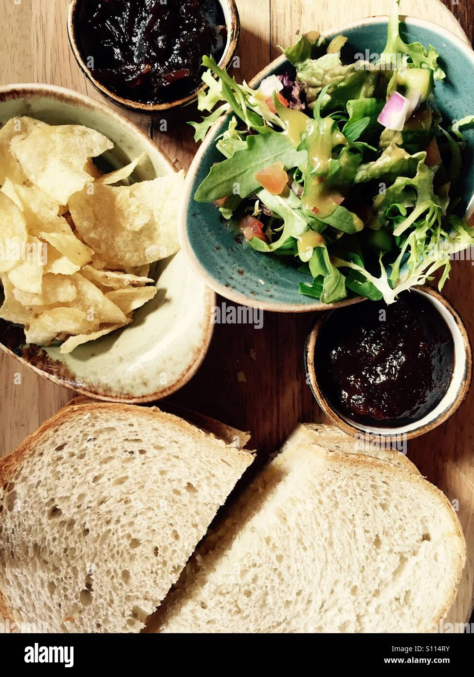 Cheese sandwich served on a wooden board with a side salad, crisps, and chutneys - Stock Image