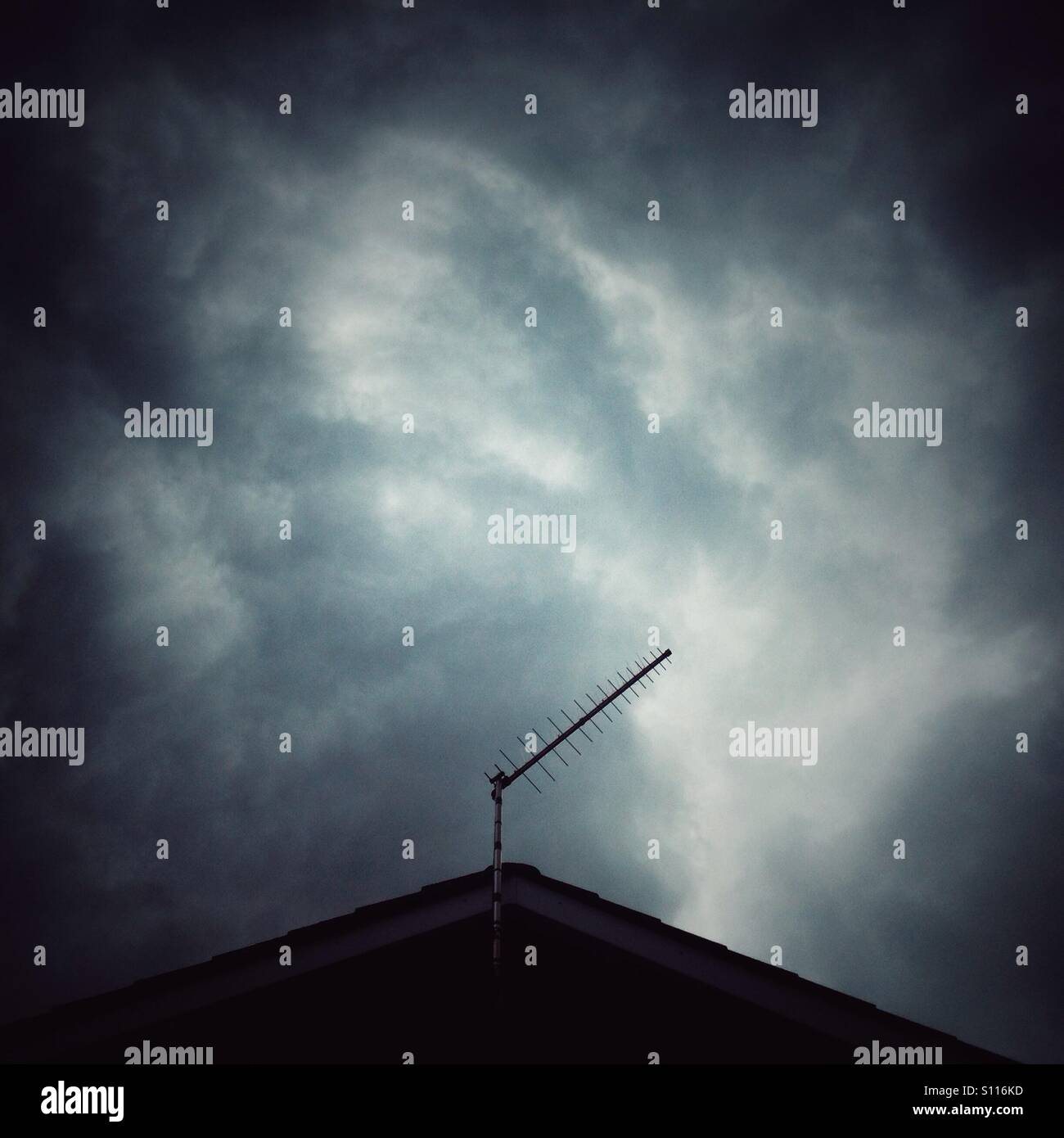 Dark clouds over a roof top of a house with a TV aerial. - Stock Image