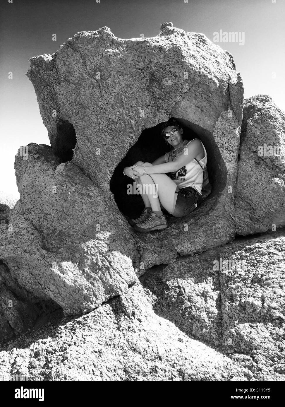 Woman shelters from the sun in a rock hollow - Stock Image