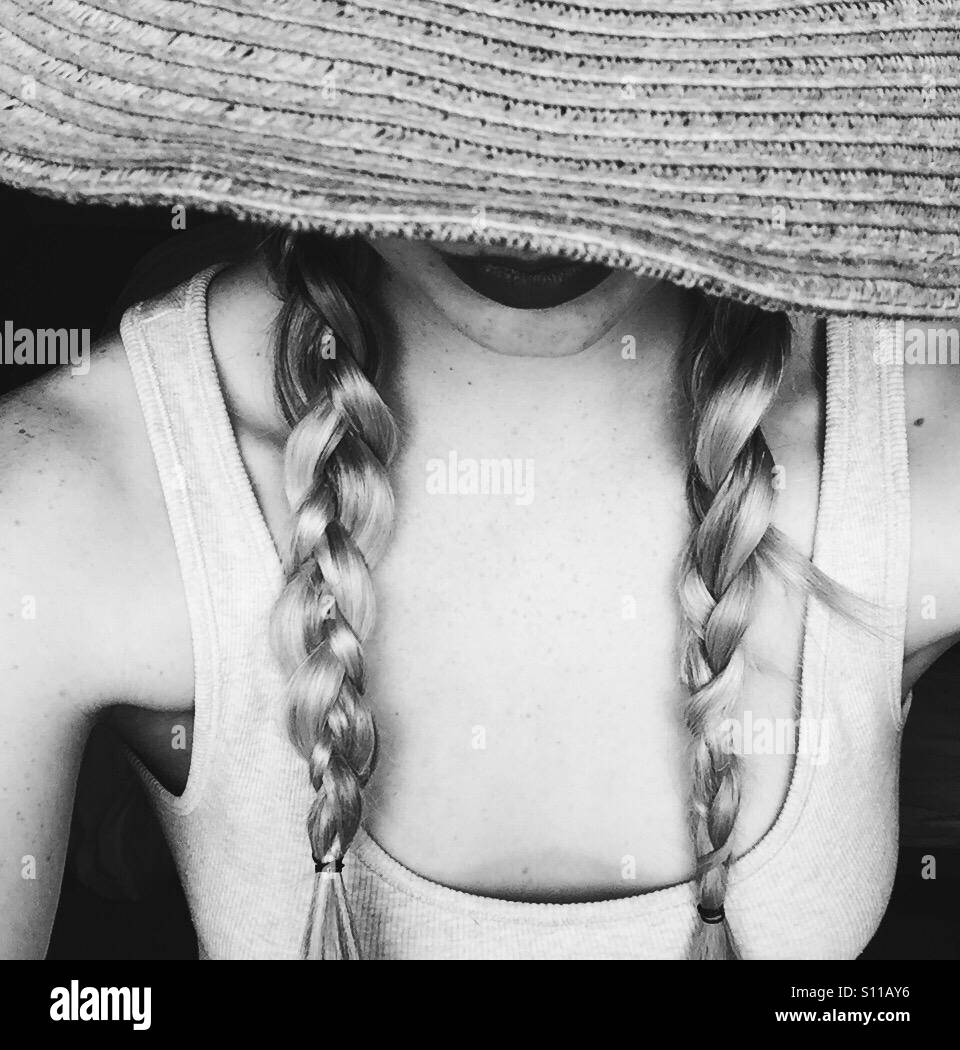 Women wearing a straw hat with plaits - Stock Image