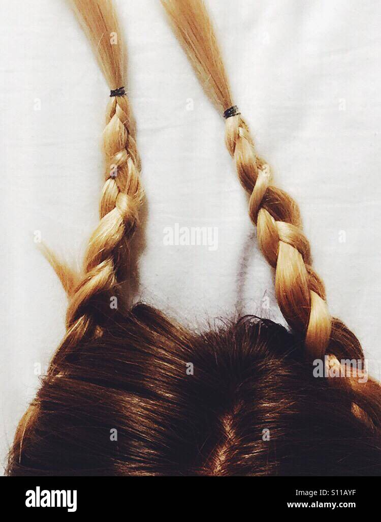 Girls hair in two plaits - Stock Image