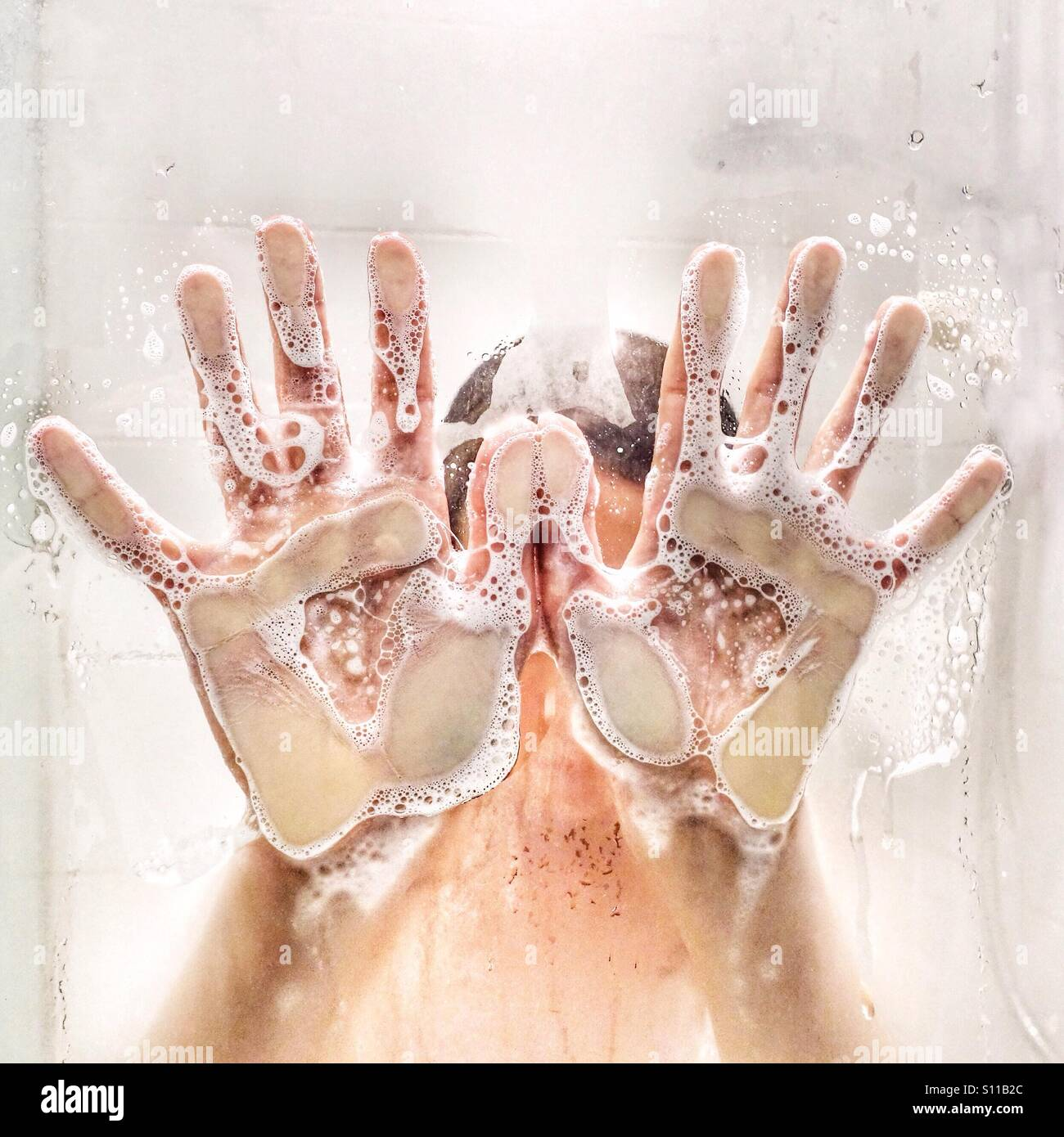 Child's soapy hands pressed against shower door - Stock Image