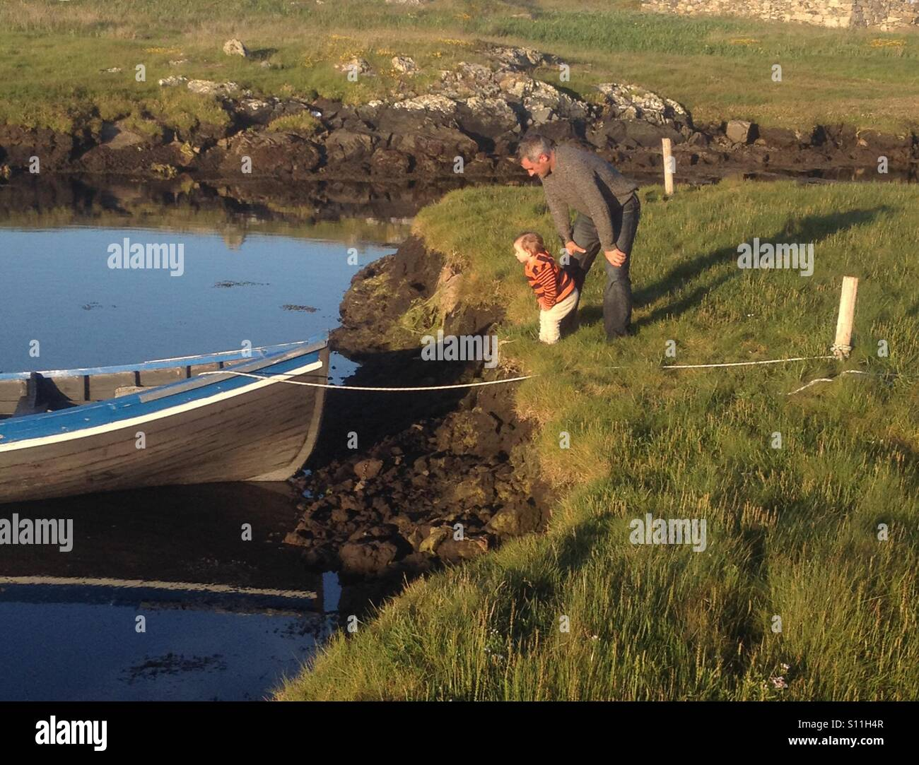 Father and son look at a wooden fishing boat tied up in a small stream in Ireland. Traditional Irish curragh is - Stock Image