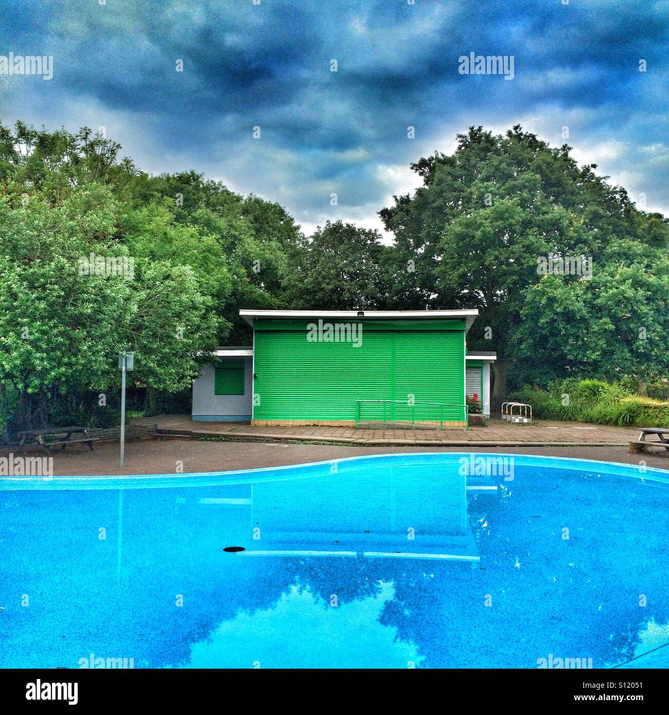 A green building by a blue paddling pool - Stock Image