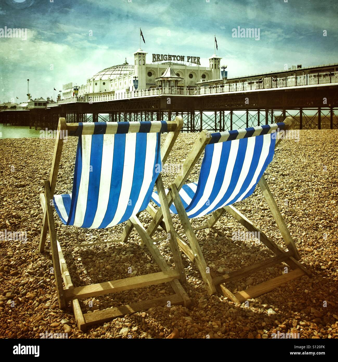 Blue and white striped deckchairs on brighton beach - Stock Image