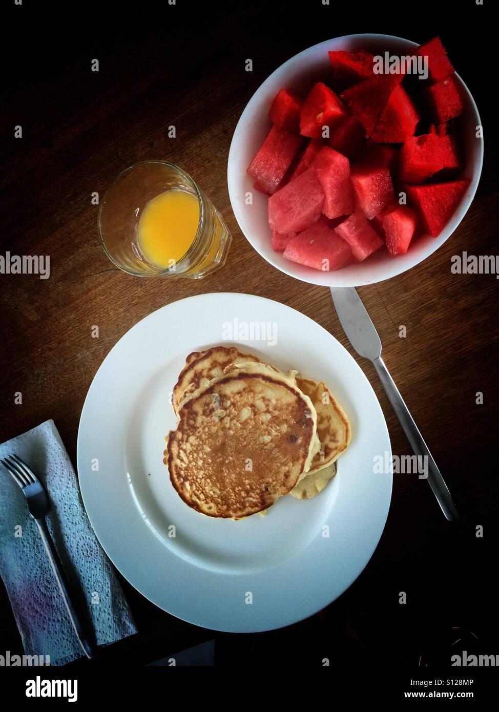 Pancakes, watermelon, and orange juice - Stock Image