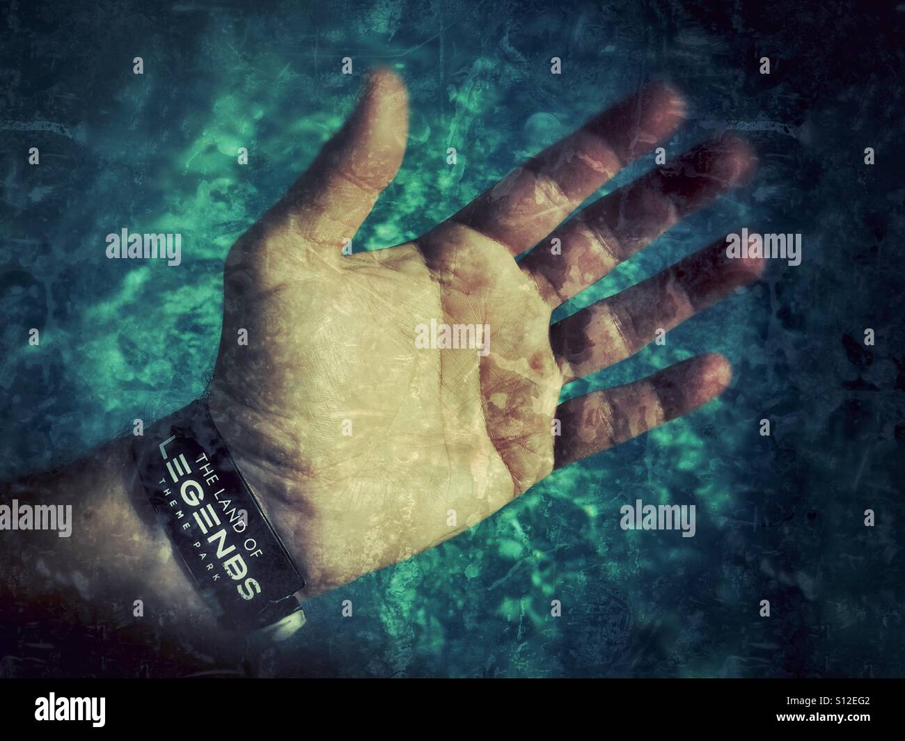 Outstretched Hand with Land of Legends Theme Park Entry Wristband on against a Watery Background. Stock Photo