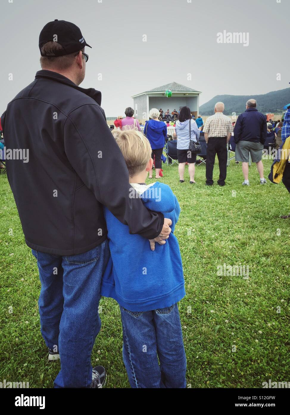 Father and son enjoy the entertainment at the Southern Shore Shamrock Folk Music Festival in Ferryland, Newfoundland, - Stock Image