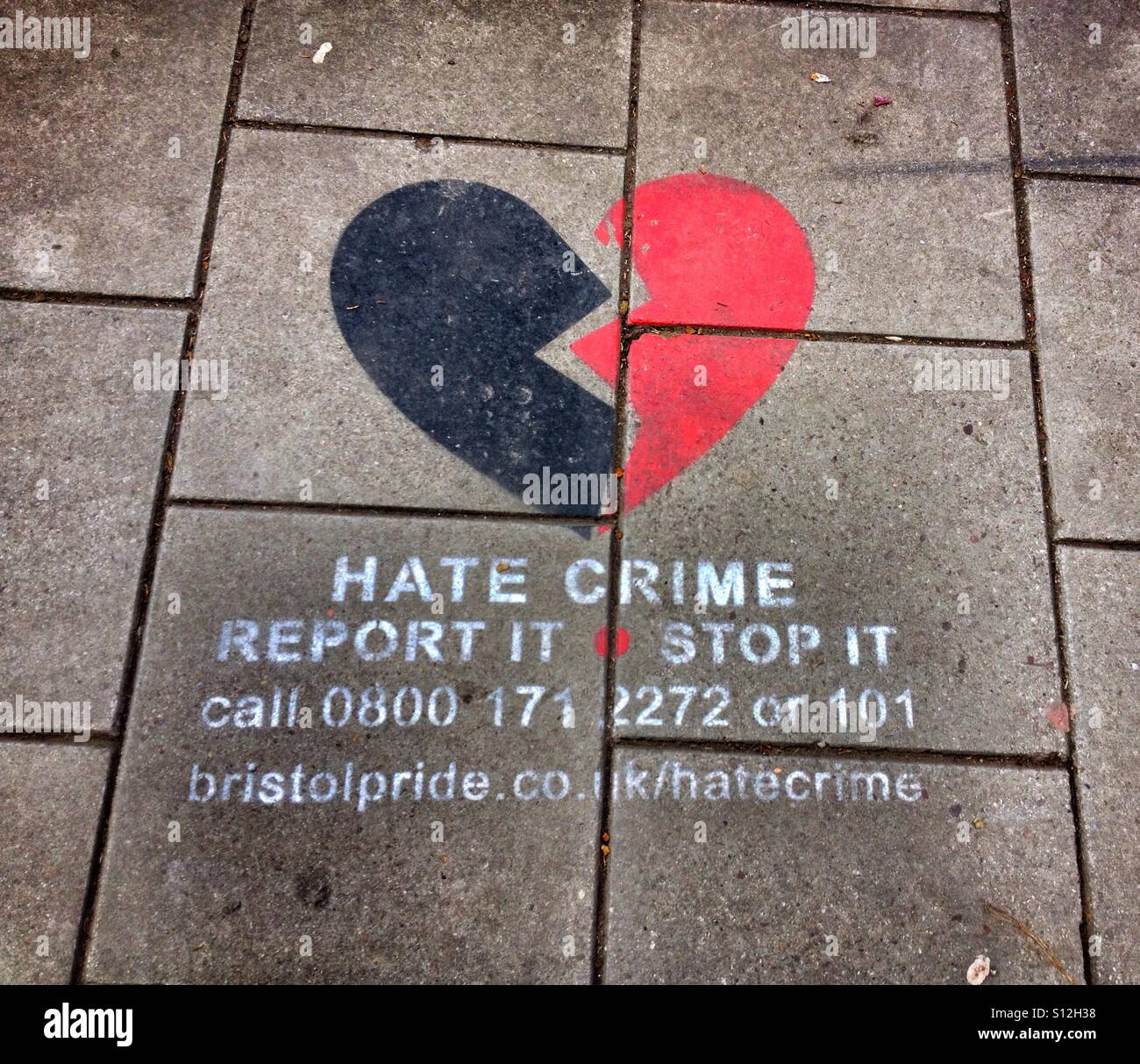 Graffiti on a pavement in Bristol, UK urging members of the public to report hate crime - Stock Image