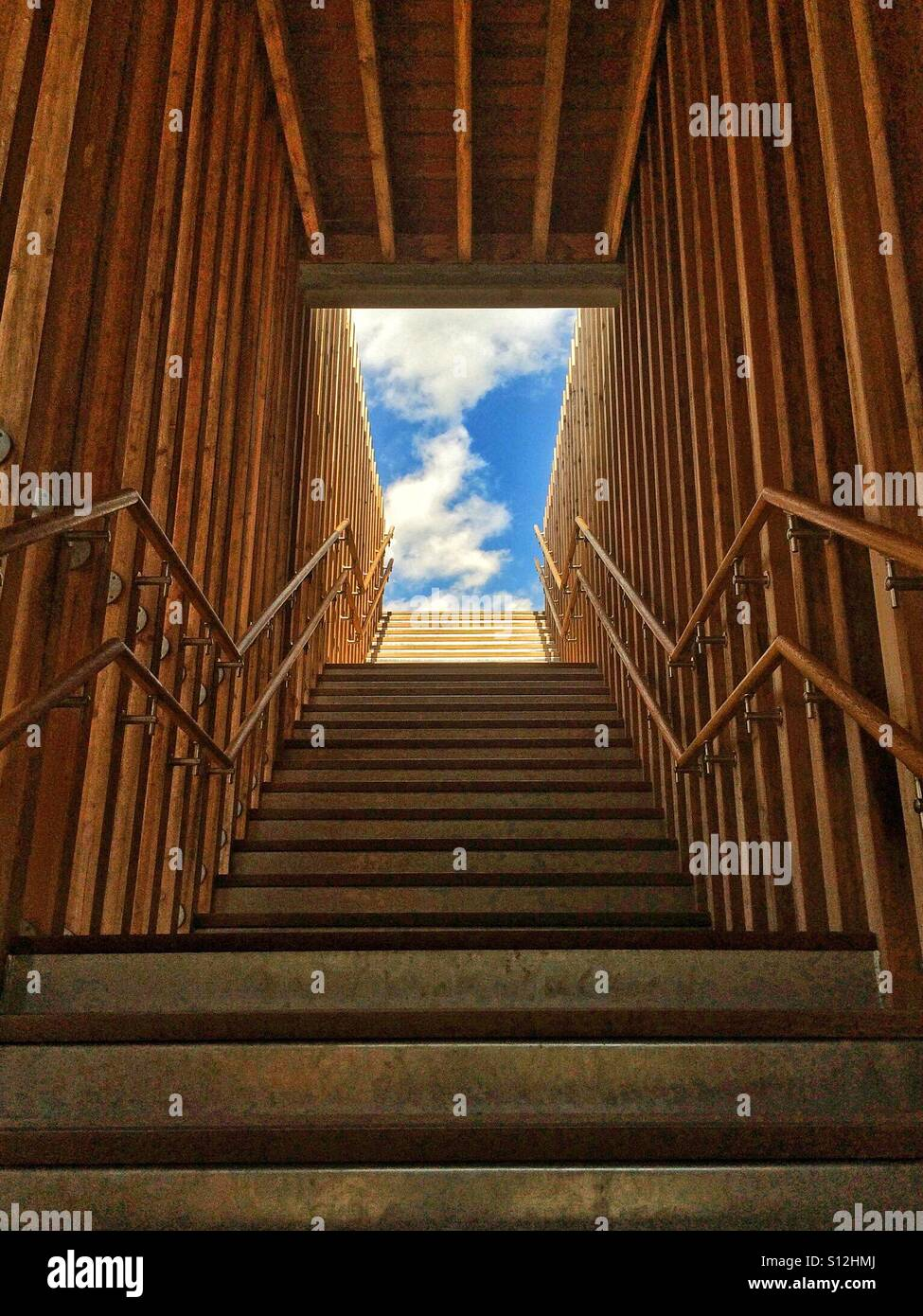 Looking up flight of stairs towards blue sky England UK - Stock Image