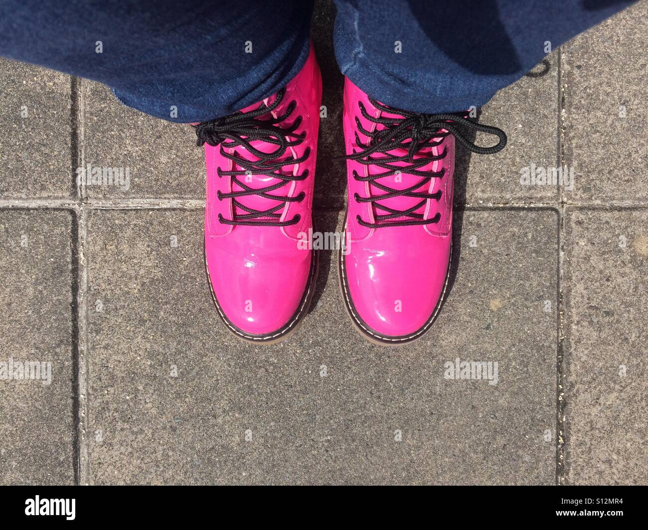 Neon pink shiny boots - Stock Image