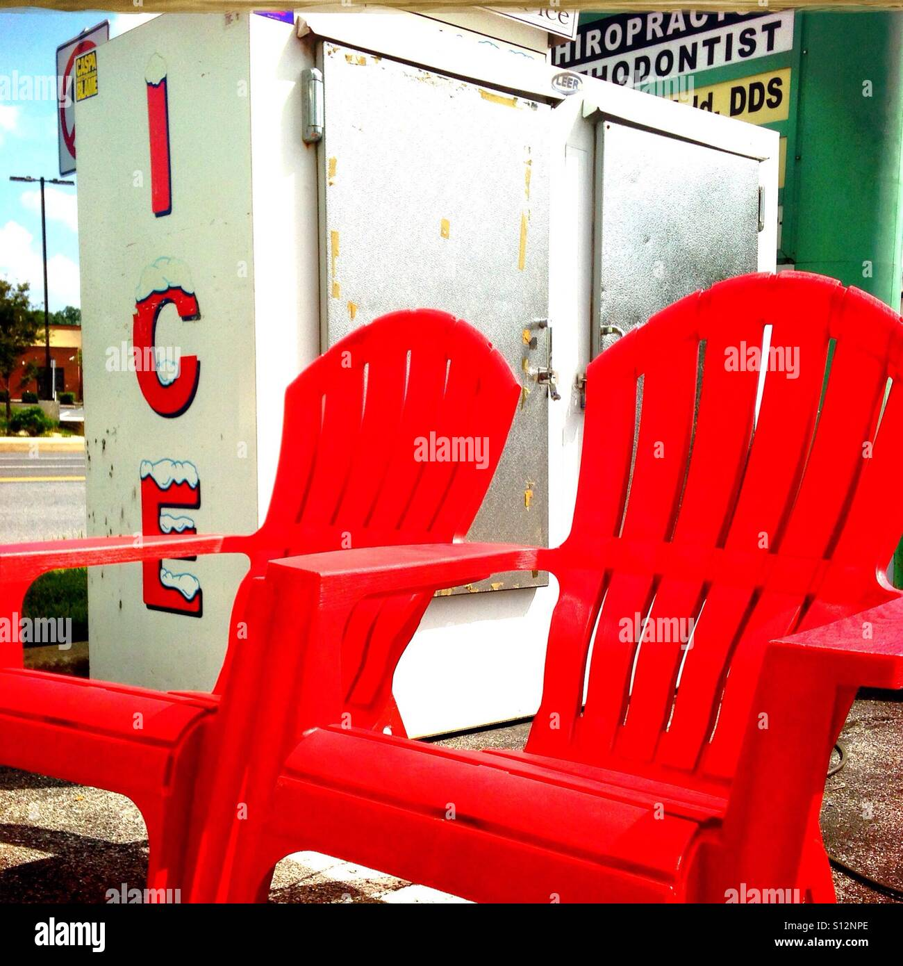 Icy red hot: An ice box next to Cherry red chairs on a hot summer day. - Stock Image