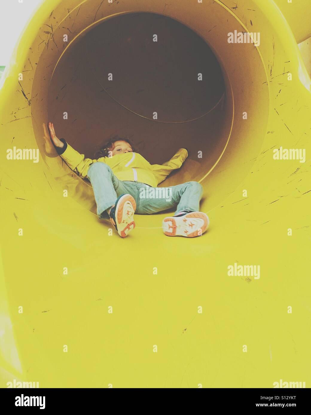 Boy coming down slide - Stock Image