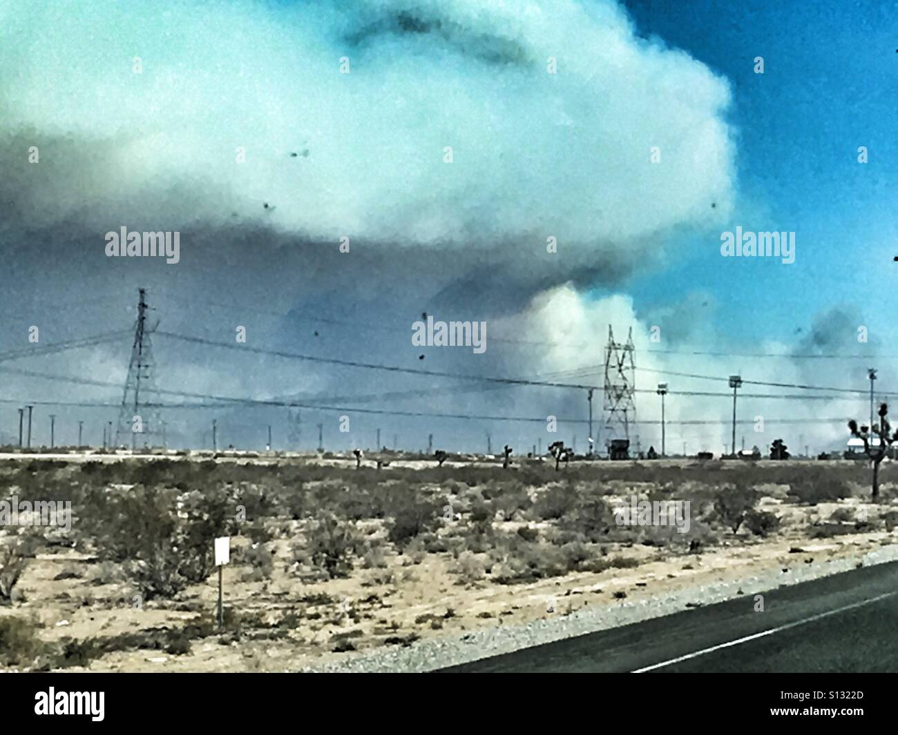 Smoke from fire blowing across the sky upon a desolate road - Stock Image