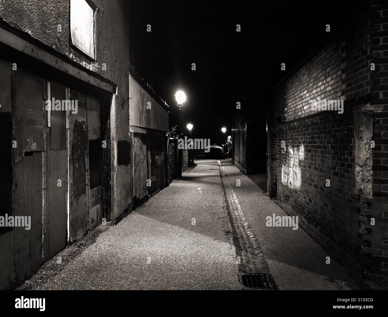 Rundown, dark, seedy and secluded back alley. - Stock Image