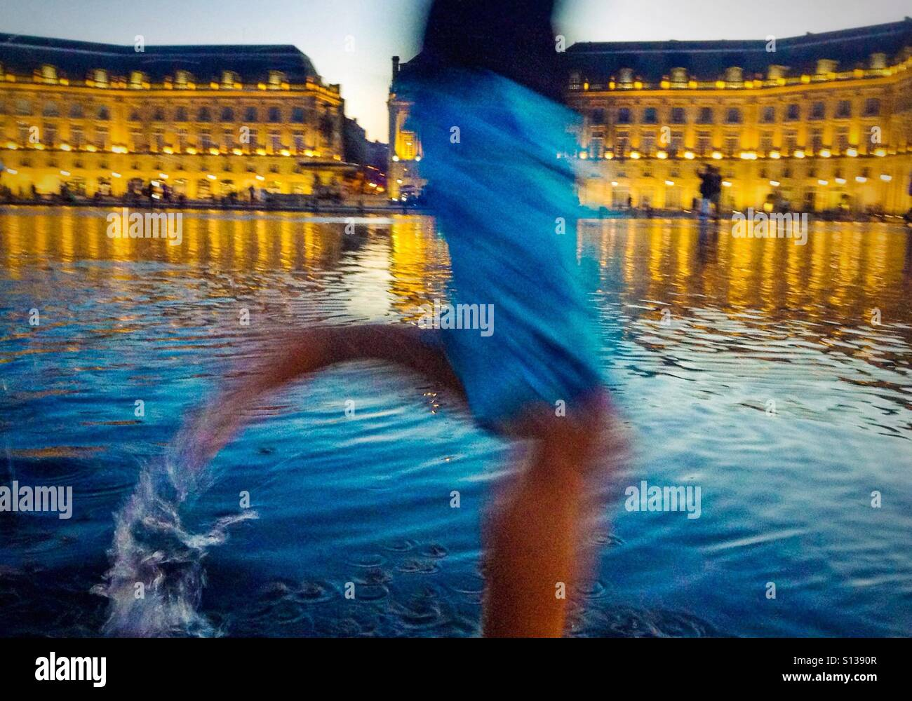 Boy running in fountain in Place de la Bourse in Bordeaux, France Stock Photo