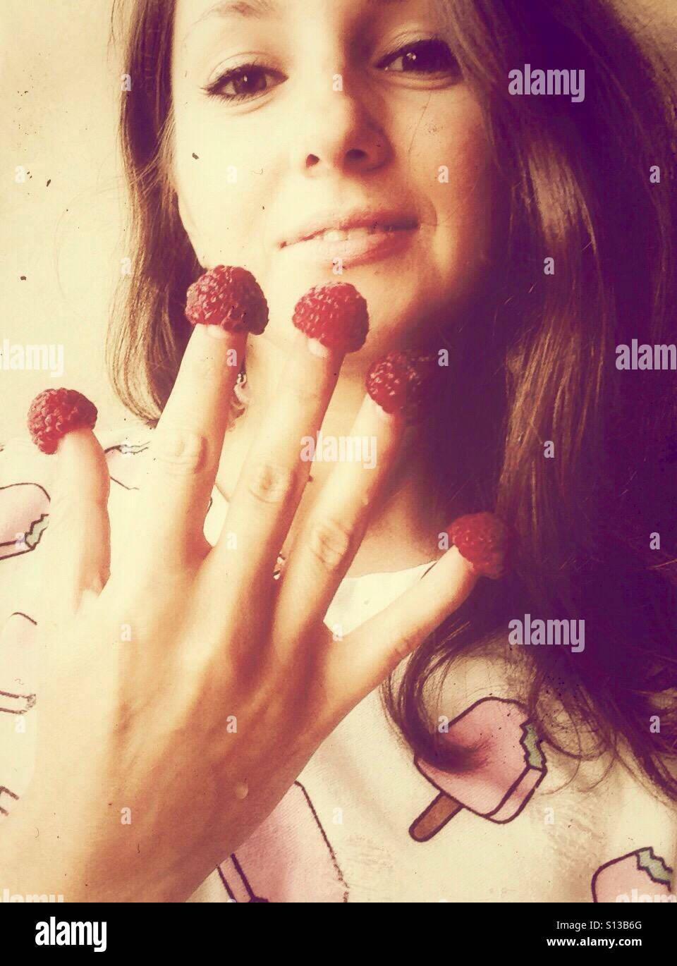 Girl with raspberries on the fingers Stock Photo