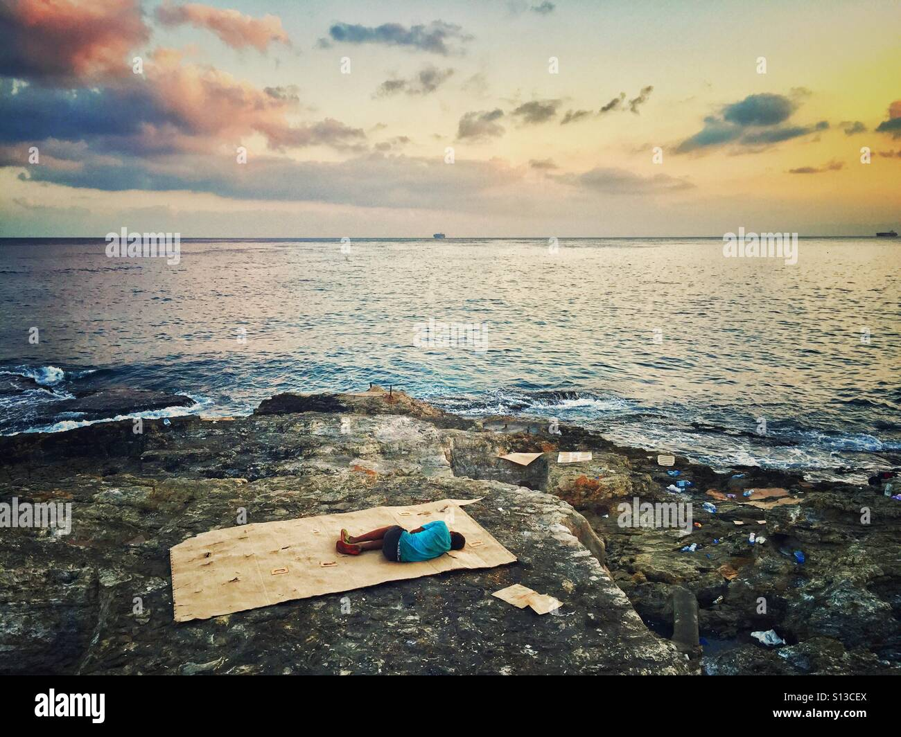 Syrian refugee child sleeping on the seashore Beirut Lebanon - Stock Image