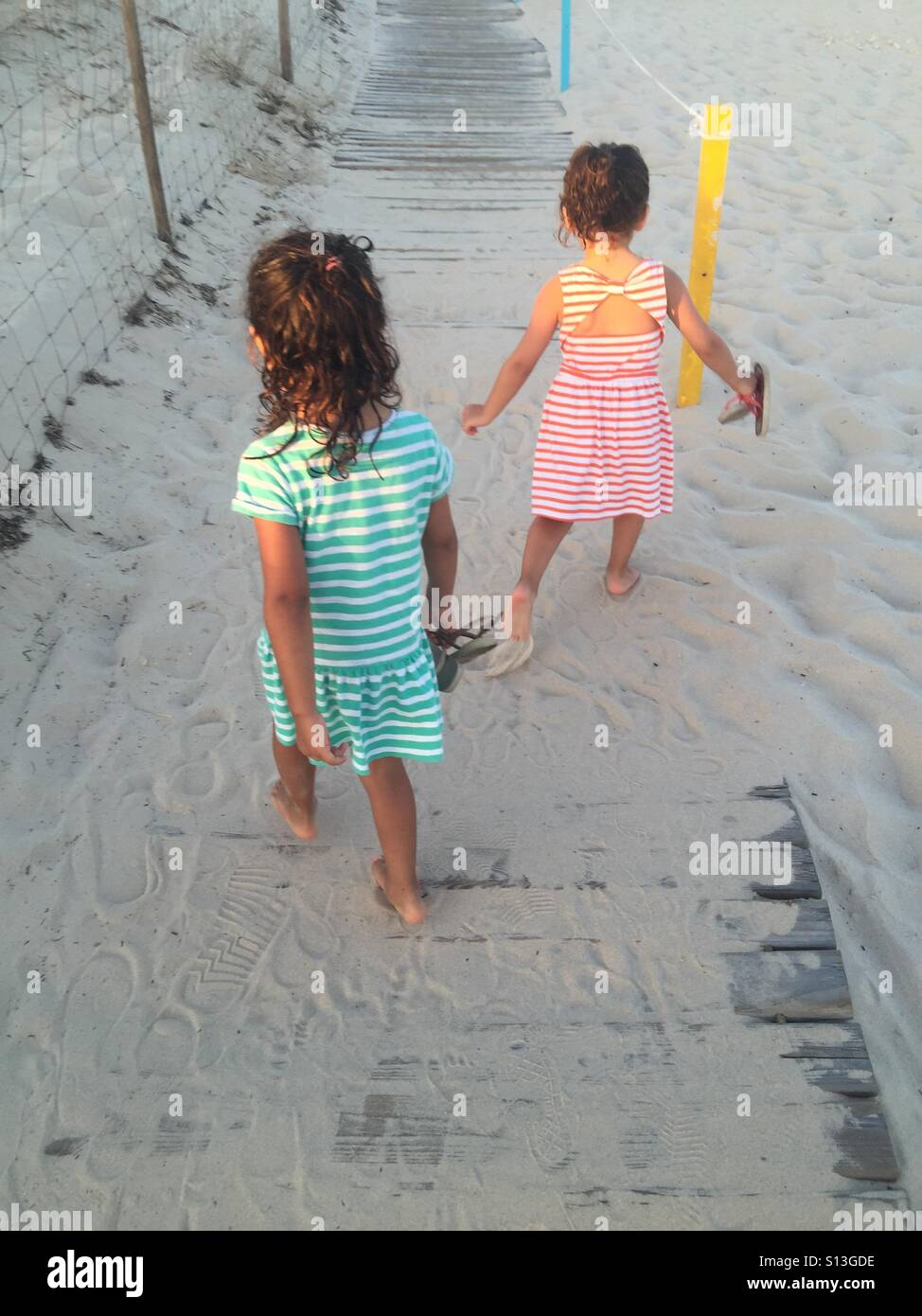 Girls walking in the sand , in stripe dresses - Stock Image